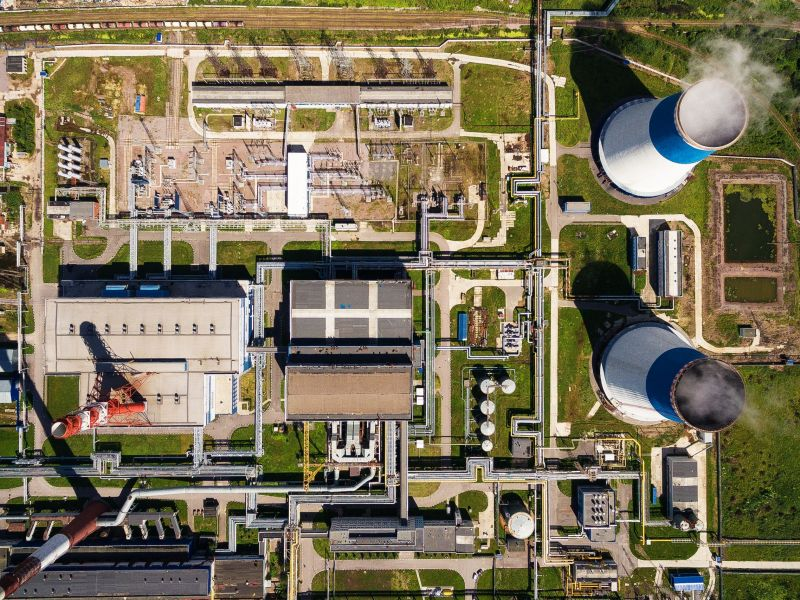 aerial view of power plant. It is on the outskirts of the city. From its two large white - blue pipe is steam. It is surrounded by greenery